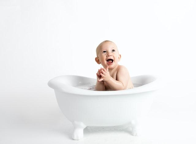 In einer kleinen weißen Badewanne sitzt ein Baby und klatscht lachend in die Hände